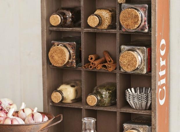 Que tal usar um engradado de madeira para guardar os temperos na cozinha? As divisórias são perfeitas para acomodar os frascos com ervas e especiarias (Foto: Elisa Correa / Editora Globo)
