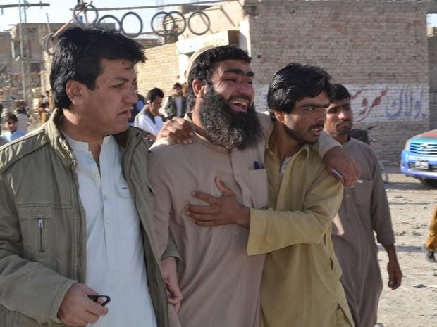 Familiares de vítima choram após ataque que deixou dezenas de mortos em Quetta, no Paquistão, nesta terça-feira (25) (Foto: Arshad Butt/ AP)