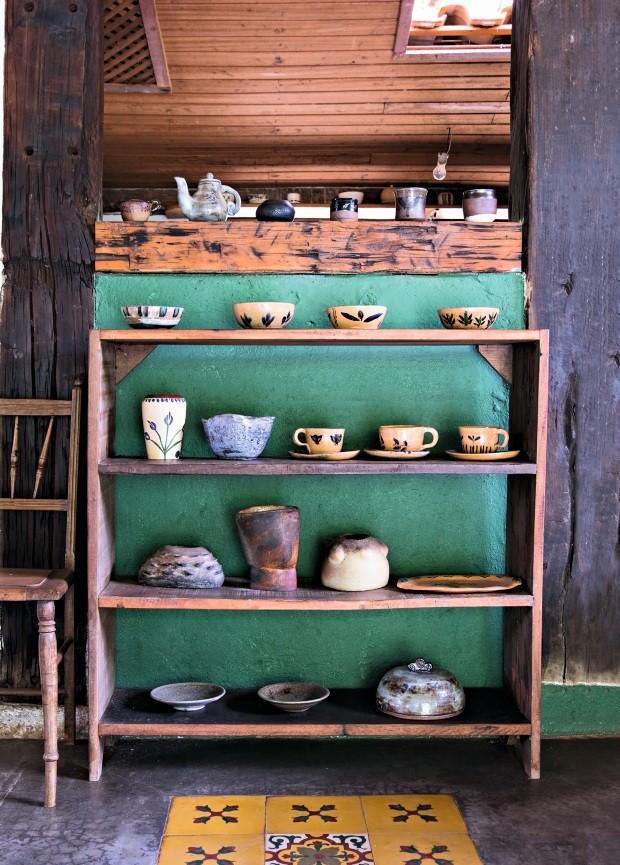 As cerâmicas ficam expostas no ateliê em frente a uma parede verde (Foto: Lufe Gomes / Editora Globo)