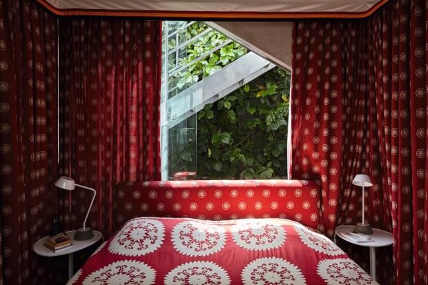 Suíte. As paredes do quarto do casal foram revestidas com tecidos em um intenso tom de vermelho, contrastando com o verde da trepadeira cissus-graúdo (Foto: Victor Affaro / Editora Globo)