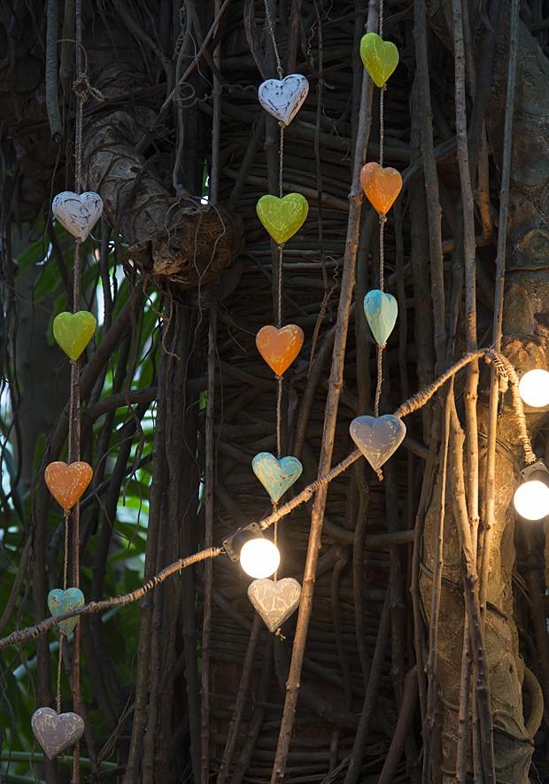 Que tal um enfeite vertical para a árvore que está no quintal? Basta escolher alguns objetos e passar um fio por eles. Nesse caso, corações coloridos, combinados com as luzes, deixaram um ar mais que romântico. Compre-os prontos ou faça em casa com gesso  (Foto: Cacá Bratke/Editora Globo)