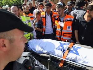 Pessoas em volta do corpo de Gilad Shaer, no funeral em sua cidade natal, Talmon, perto da cidade de Ramallah, na Cisjordânia (Foto: Menahem Kahana/ AFP)