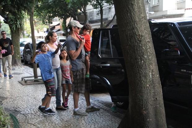 Márcio Garcia coloca as crianças no carro (Foto: Rodrigo dos Anjos/Agnews)