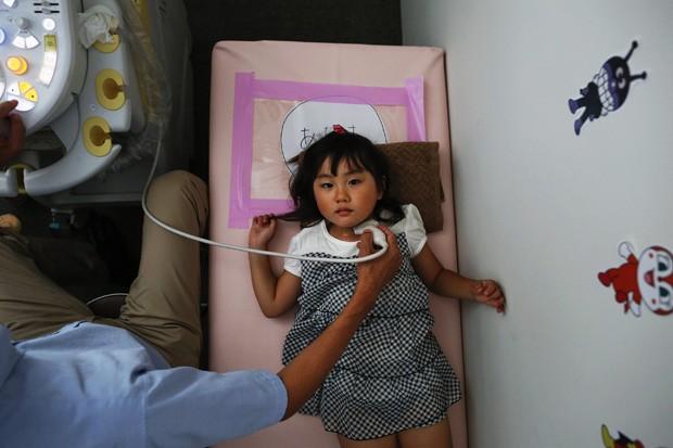 Um médico realiza um exame de tireóide na garota Maria Sakamoto, de 4 anos, levada por sua mãe ao Centro de Radiação dos Cidadãos de Iwaki, na cidade ao sul da usina de Daiicchi, em Fukushima. A OMS afirma que crianças da região tem risco mais alto de de (Foto: Reuters/Damir Sagolj)