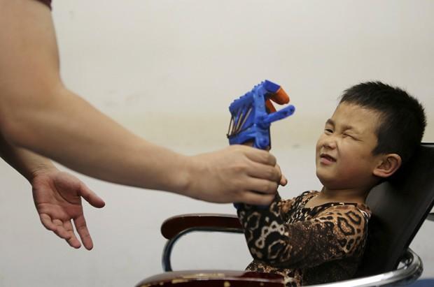 Depois de testes, garoto Xiaocheng conseguiu seguranr objetos leves com sua prótese feita em impressora 3D (Foto: Reuters/Stringer)