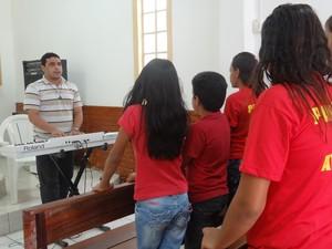 Professor de música com os alunos do coral (Foto: Michelle Farias/G1)