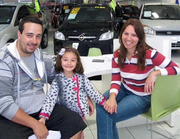 Juliana, Fernando e a filha Giovana concluem a compra do carro novo da família: carro maior vai render prestação mais barata que o antigo. (Foto: Simone Cunha/G1)