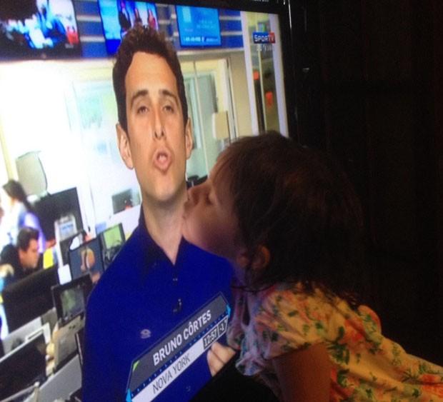 Julia, 4 anos, filha de Bruno, beijando o pai através da televisão (Foto: Arquivo Pessoal)
