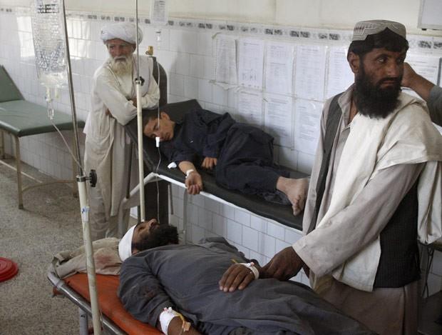 Afegãos confortam parentes feridos em três explosões que atingiram o distrito de Arghistan district, as they receive treatment at civil hospital in Chaman, na fronteira com o Paquistão (Foto: Matiullah Achakzai / AP)