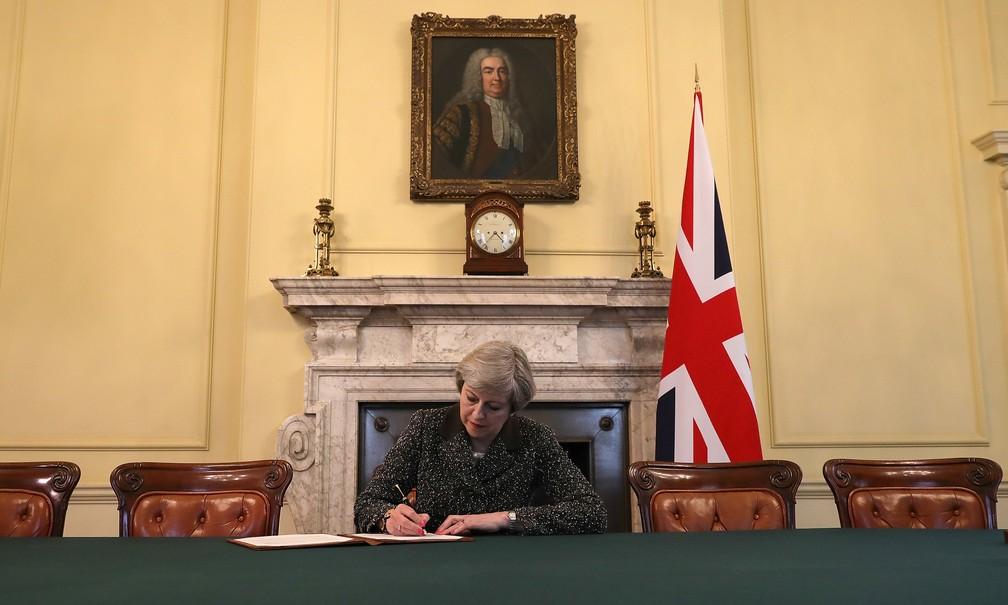 A premiê Theresa May, sentada sob um retrato de Robert Walpole, primeiro a ocupar o cargo, assina a carta invocando o Artigo 50, para a saída britânica do Reino Unido (Foto: Christopher Furlong/Reuters)