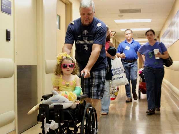 Menina é guiada em uma cadeira de rodas a partir de seu quarto no hospital por seu pai, Jerry Nugent (Foto: AP Photo / The Tampa Tribune, Andy Jones, Pool)