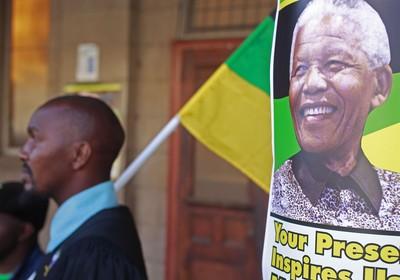 Um homem está ao lado de um cartaz de Nelson Mandela durante no Congresso Nacional Africano, onde ocorre uma reunião de oração ao ex-presidente da África do Sul (Foto: AP Photo/Schalk van Zuydam)
