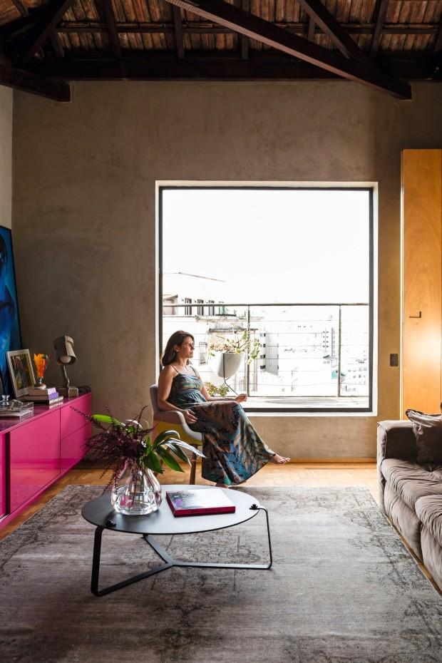 Sala de estar. A moradora, Fúlvia Oliveira, está sentada na poltrona East River, da Vitra. O rack pink foi executado pela marcenaria ArtMóveis. Tapete da Botteh Handmade Rugs e mesa de centro da Carbono com vaso da Marché Art de Vie (Foto: Edu Castello / Editora Globo)