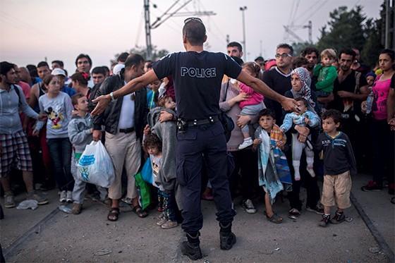 3. Um policial impede a entrada de refugiados  na Macedônia (Foto: AP Photo/Santi Palacios Szabo)