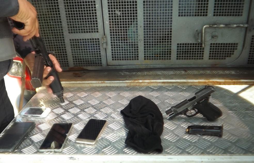 Pistola, munições, capuz e celulares foram apreendidos com os suspeitos (Foto: Divulgação / PM)