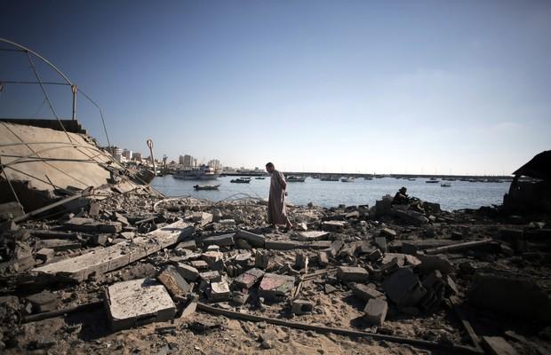 Homem caminha em meio a destroços após ataque de Israel a uma praia em Gaza. Ataque matou 4 crianças (Foto: Khalil Hamra/AP)