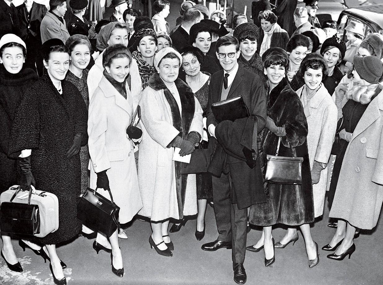 Victoire na entrada da Victoria Station, em Londres, com Saint Laurent (ela está à esquerda dele) e staff antes do desfile de alta-costura da Dior no Blenheim Palace, em 1958 (Foto: Mark Shaw e Divulgação)
