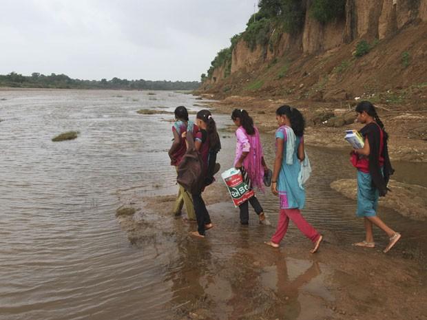 Alguns pais acompanham os filhos na travessia do rio (Foto: Ajit Solanki/AP)