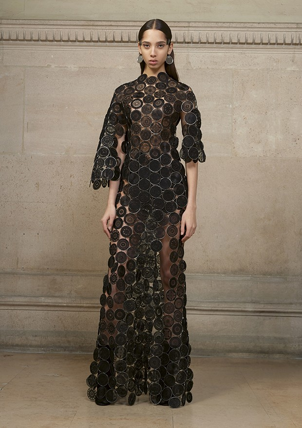 Yasmin wears a long asymmetric dress made entirely of fine metal rings covered with organza and hand-embellished with geometric motifs (Foto: Givenchy)