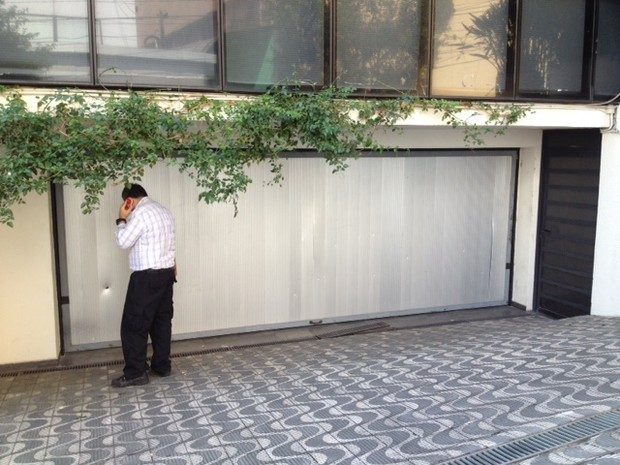 Buraco (do lado esquerdo) e fissura (do lado direito) no portão do instituto lula causados por bomba  (Foto: Kleber Tomaz/G1)