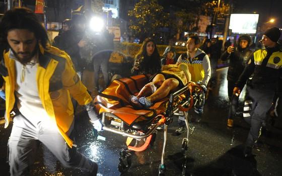 Socorrista resgata vítimas do atentado na boate Reina em Istambul (Foto: IHLAS NEWS AGENCY / AFP)
