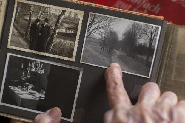 Margot Woel mostra um velho álbum de fotos e aponta para uma foto tirada do caminho para a 'Toca do Lobo' (Foto: Markus Schreiber/AP)