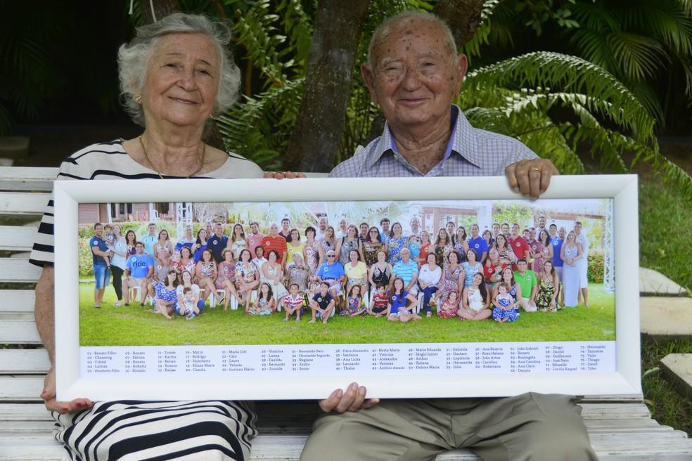 Dona Dezilda e seu Zezito mostram, orgulhosos, o quadro com todos os filhos, netos e bisnetos (Foto: Andréa Tavares/G1 )