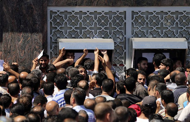 Dezenas de palestinos aguardam para sacar dinheiro em banco da cidade de Gaza nesta quinta-feira (17) (Foto: Mohammed Salem/Reuters)