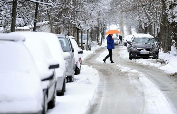 Mulher anda em região coberta de neve na parte de Buda de Budapeste, na Hungria (Foto:  Attila Kisbenedek/AFP)