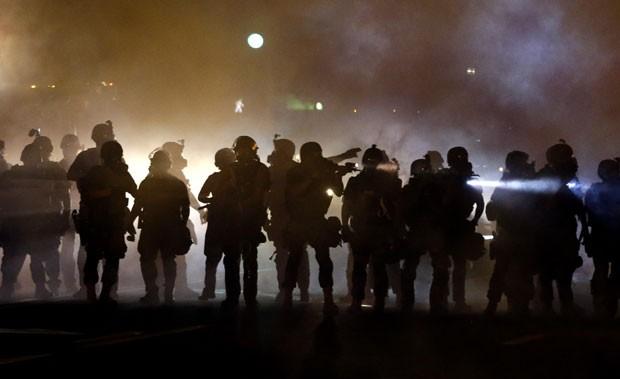 Policiais são vistos durante confronto com manifestantes em Ferguson, no Missouri, nesta quarta-feira (13) (Foto: Jeff Roberson/AP)
