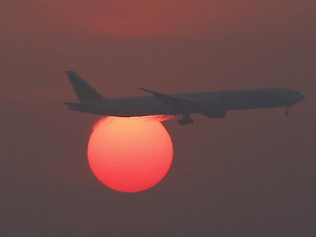 Avião é visto em frente ao sol poente sobre o Aeroporto Internacional de Pequim, na China (Foto: Kim Kyung-Hoon/Reuters)