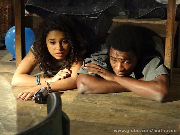 Com medo, Julia e Frédéric se escondem embaixo de uma cama no abrigo (Foto: Malhação / TV Globo)