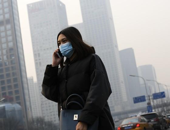 Chineses enfrentam dia de forte smog, uma nuvem de poluição do ar, em Pequim, China. Autoridades emitiram novos alertas sobre riscos da poluição (Foto: Andy Wong/AP)
