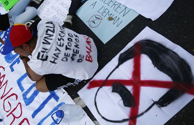 Manifestantes antigoverno exibem cartazes durante protesto nesta quinta-feira (13), em Caracas (Foto: Jorge Silva/Reuters)