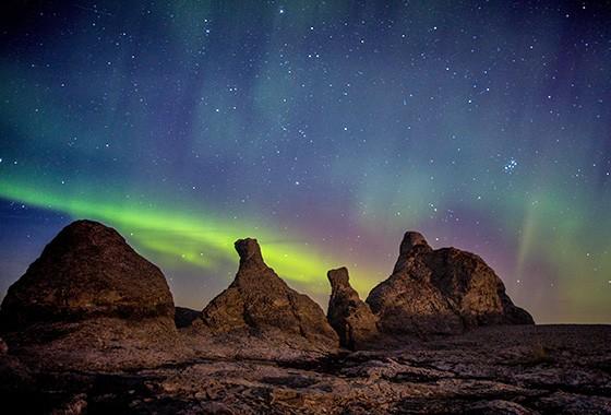 Aurora boreal na Praia dos Trolls, na Noruega; as formações rochosas assemelham-se a figuras antropomórficas da mitologia nórdica  (Foto:  )