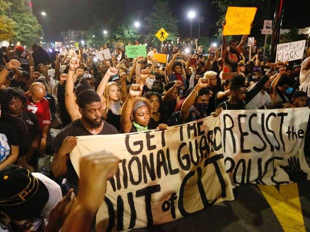 Manifestantes desafiam toque de recolher e se ajoelham durante protesto em Charlotte (Foto: Jason Miczek / Reuters)