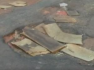 Moradores colocaram tábuas de compensado nos buracos para diminuir o impacto  (Foto: Reprodução/TV TEM)