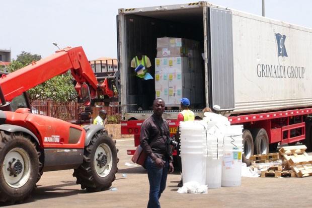 Integrantes do Médicos Sem Fronteiras descarregam equipamentos médicos para tratar epidemia de ebola na guiné neste domingo (23)  (Fot Saliou Samb/Reuters)