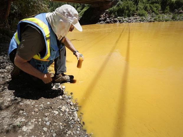 Especialista colhe amostra da água do rio Animas. Contaminação por metais pesados afeta população local (Foto: Jerry McBride/The Durango Herald via AP)