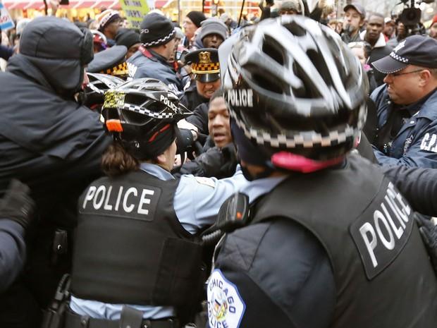 Policiais detém um manifestante em protesto que pedia a renúncia do prefeito de Chicago, Rahm Emanuel, na quinta (24) (Foto: AP Photo/Charles Rex Arbogast)