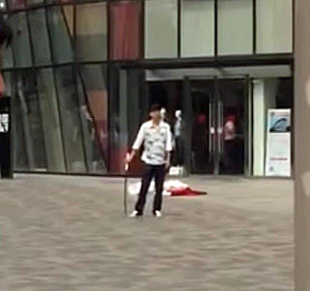 Homem segura espada após ter matado uma mulher e ferido outra pessoa; em seguida ele seria detido (Foto: Reprodução/Youtube/Loser Laowai)