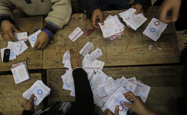 Funcionários contabilizam cédulas do referendo que deve legitimar a nova Constituição egípcia, nesta quarta-feira (15) (Foto: Amr Nabil/AP)