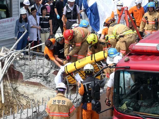 Bombeiros retiram corpo de um trabalhador de instalação destruída (Foto: Kim Yong-tae / Yonhap / via AP Photo)