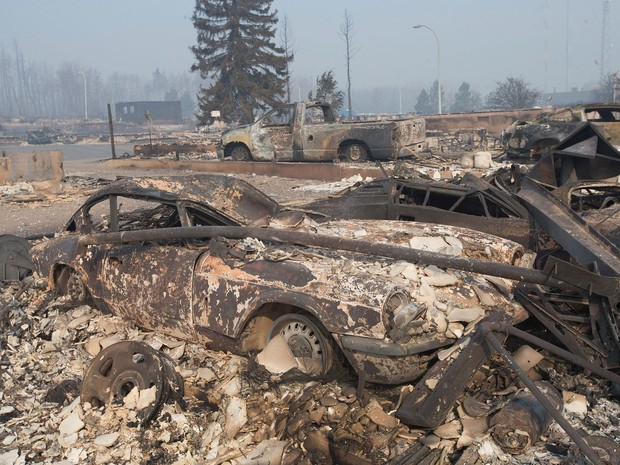Restos de um Triumph GT6 carbonizado são vistos em bairro residencial destruído por incêndio em Fort McMurray, em Alberta, no Canadá, na sexta (6) (Foto: Scott Olson/Getty Images/AFP)