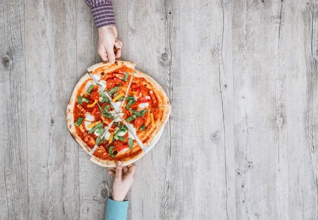 Duas pessoas dividindo uma pizza (Foto: Thinkstock)