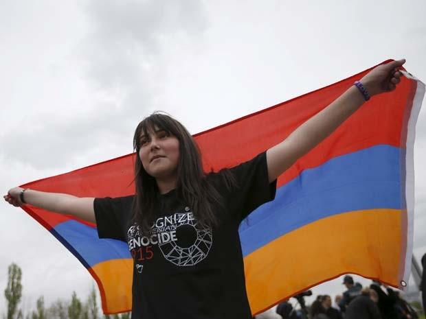 Jovem segura bandeira da Armênia em frente a memorial em Erevan nesta terça-feira (21) (Foto: REUTERS/David Mdzinarishvili)