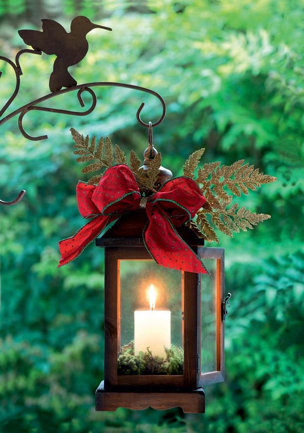 Um laço vermelho e alguns galhinhos já são o suficiente para dar um toque natalino à lanterna de ferro. Um ninho de musgos completa a decoração  (Foto: Iara Venanzi/Editora Globo)