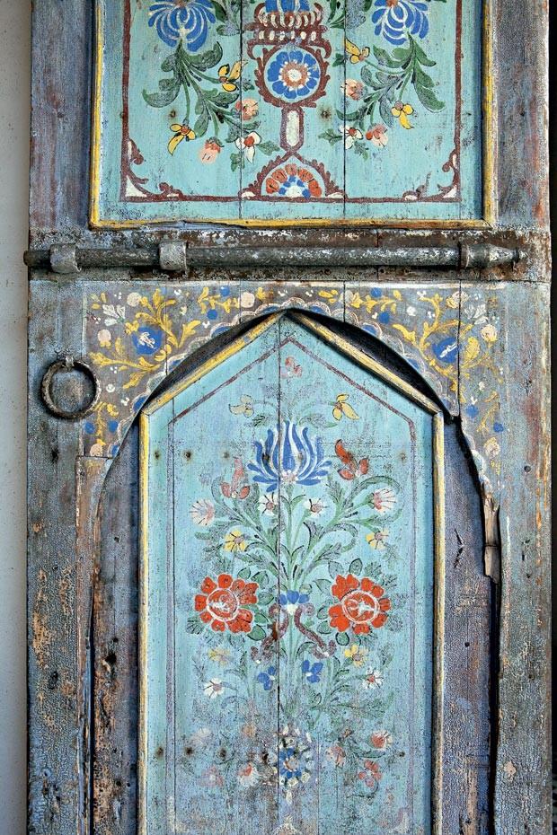 O quarto do casal fica no segundo piso. Veja a delicadeza da pintura original de flores na porta (Foto: Lufe Gomes/Life by Lufe)