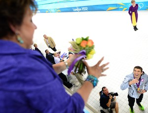 Michael Phelps joga flores para sua mãe após 4x100m medley nos Jogos de Londres (Foto: Christophe Simon/AFP)