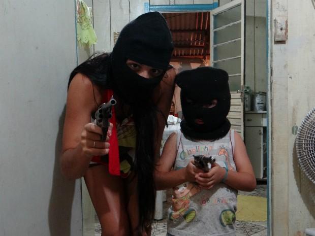 Foto da adolescente e da criança com capuzes e segurando armas estava em uma máquina fotográfica apreendida pela PM em uma casa em Terra Roxa (PR) (Foto: Polícia Militar / Divulgação)